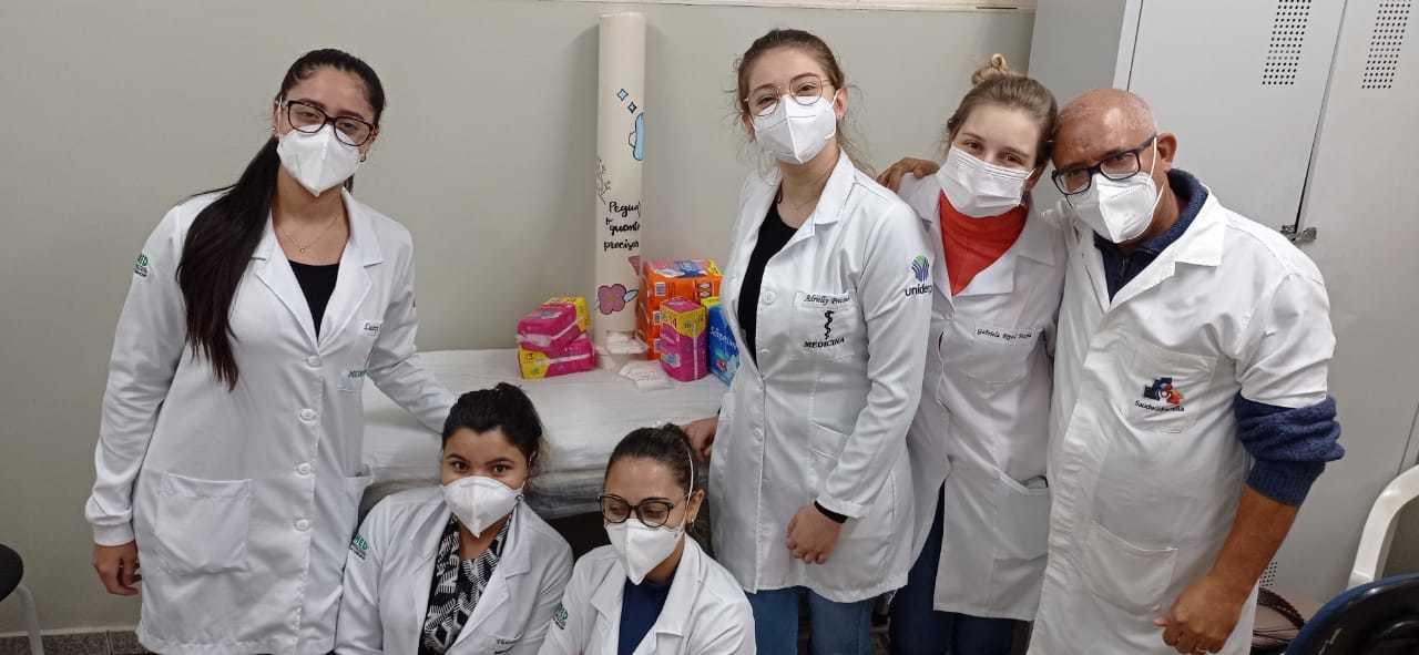 Estudantes e profissionais de saúde com o dispenser com absorventes feitos na USF Mata do Jacinto. (Foto: Reprodução Redes Sociais Sesau)