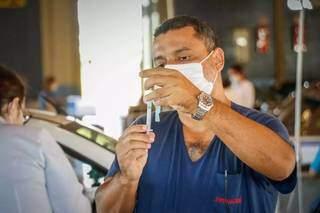 Momentos antes de vacinar alguém, enfermeiro prepara dose de imunizante contra covid (Foto: Henrique Kawaminami/Arquivo)
