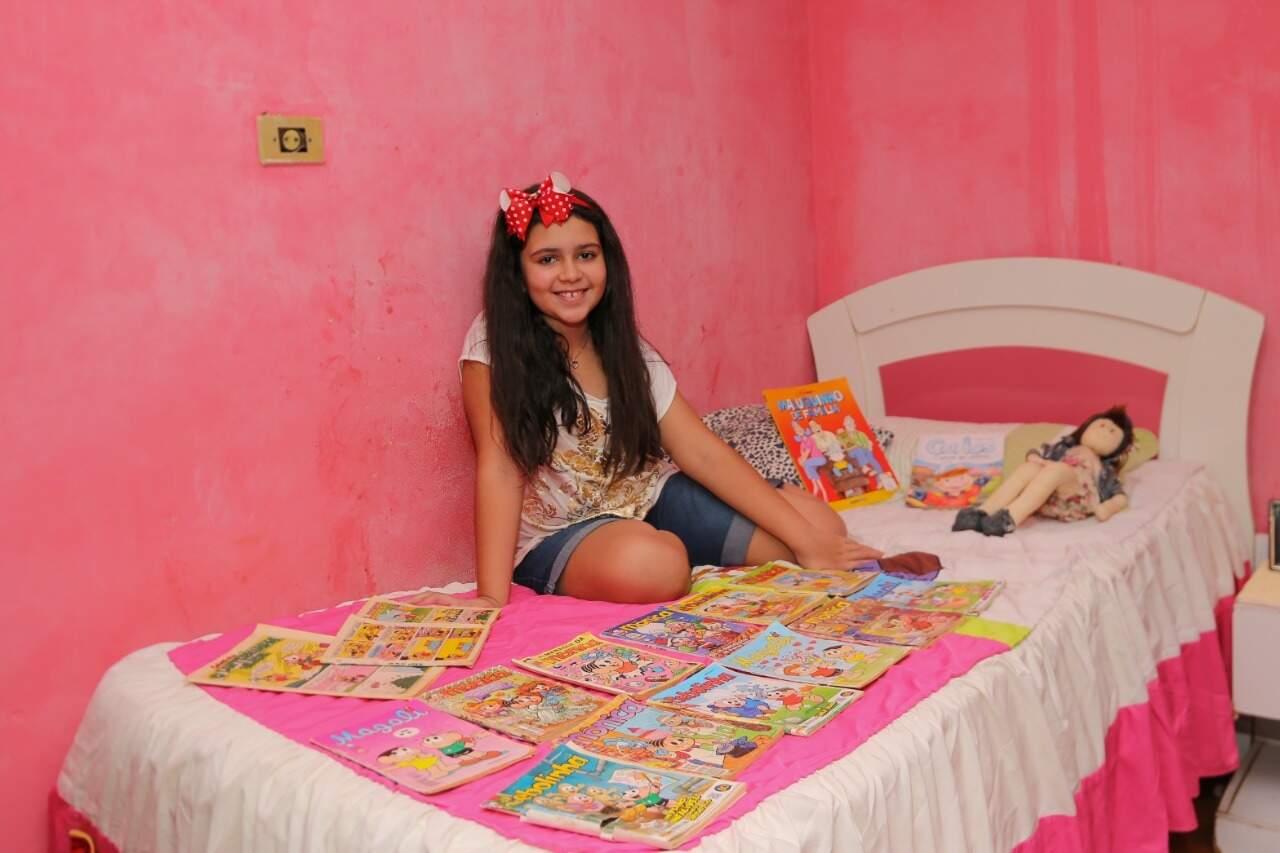 Sentada em sua cama dentro do seu quarto rosa, Isabella não esconde a felicidade ao estar perto dos gibis. (Foto: Paulo Francis)