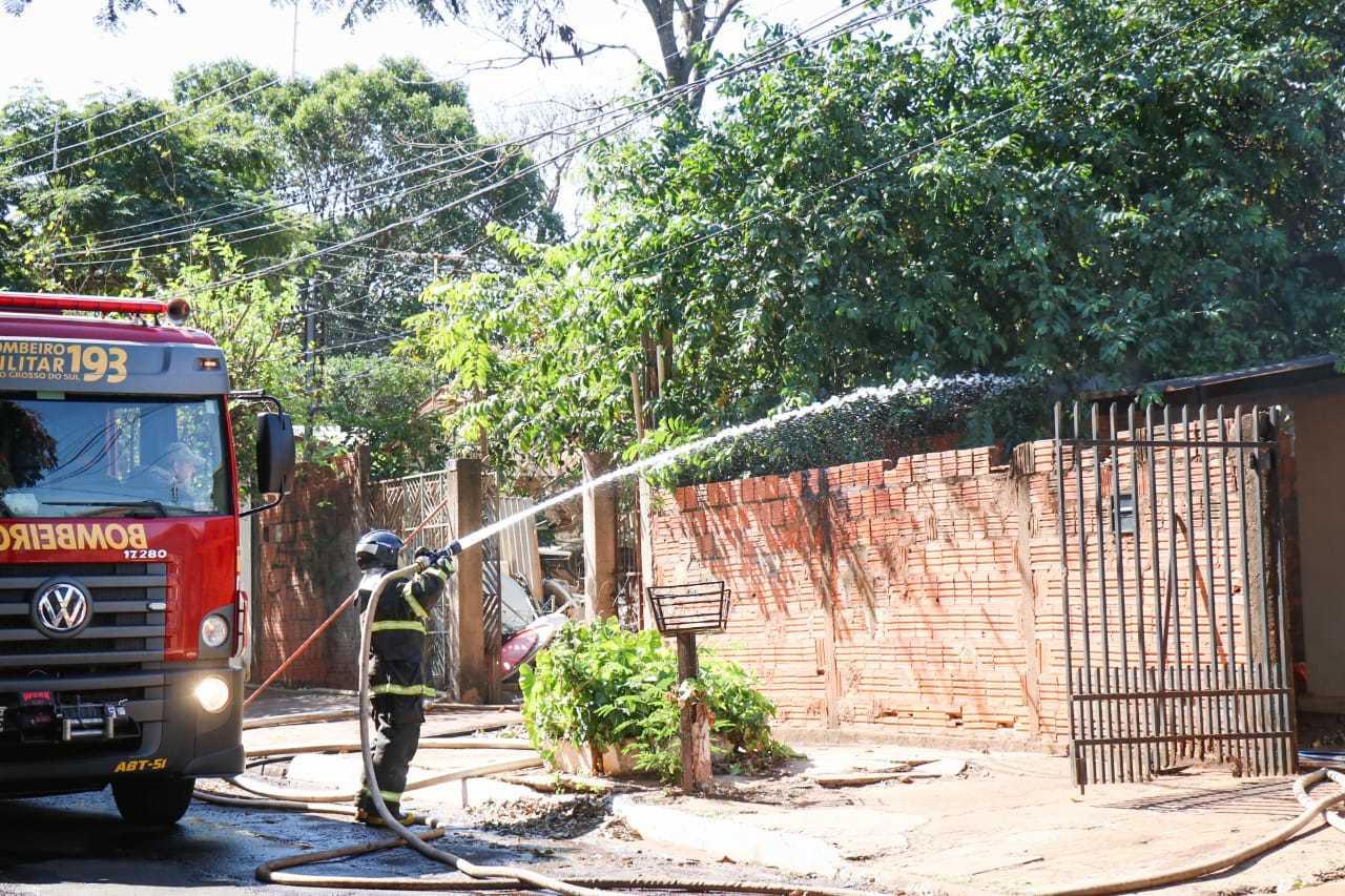Bombeiro jogando água dentro da casa para controla incêndio. (Foto: Henrique Kawaminami)