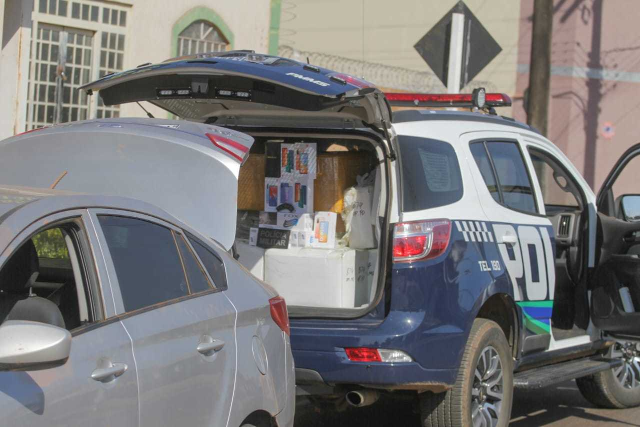 Porta-malas do carro e da viatura abertos, com o veículo da polícia já com o contrabando. (Foto: Marcos Maluf)