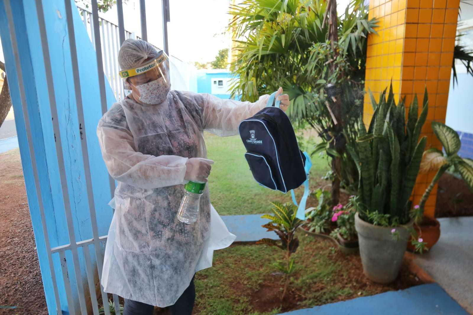 Mochilas são higienizadas com álcool antes dos pequenos entrarem na escola. (Foto: Paulo Francis)