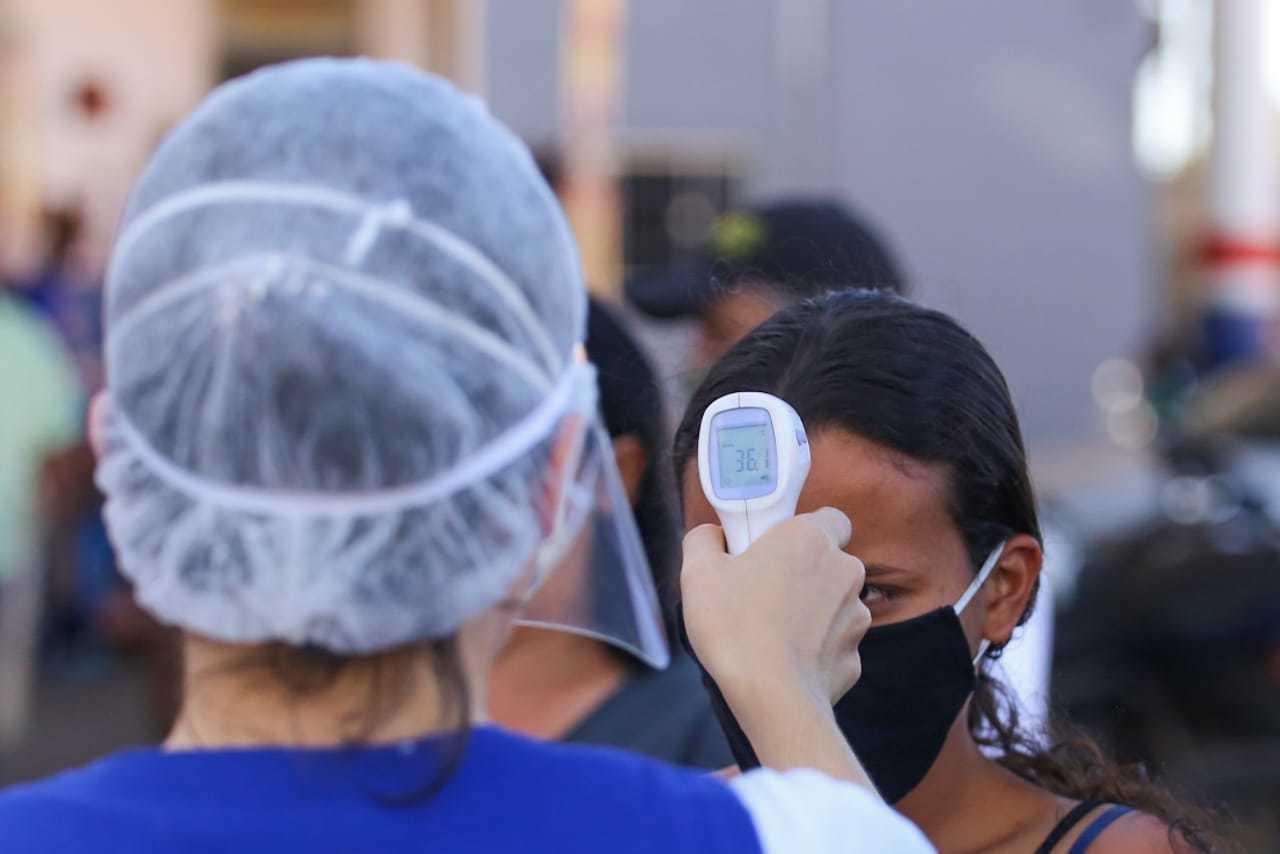 Servidora da saúde aferindo temperatura de moradora na Capital. (Foto: Marcos Maluf)