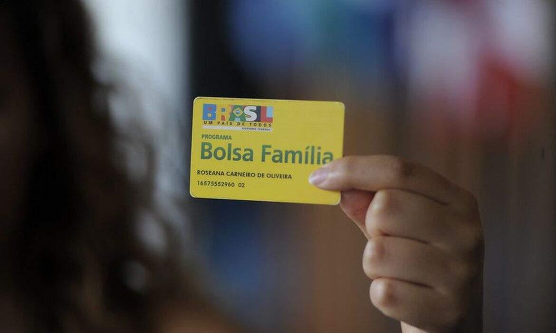 Beneficiária segura cartão do programa federal (Foto: Agência Senado)