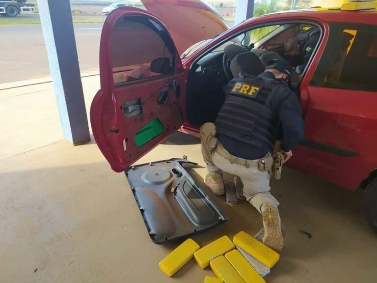Policiais retirando as drogas dos fundos falsos do veículo. (Foto: PRF)