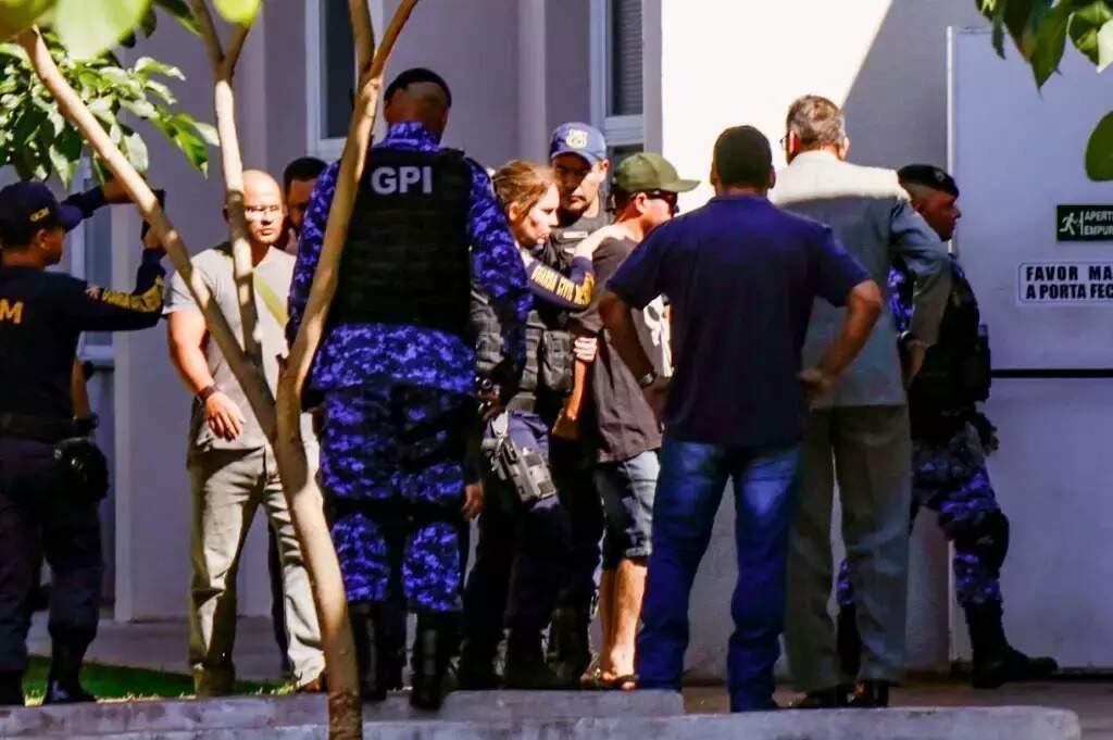 Guarda chegando na delegacia de bermuda, chinelo, camiseta, usando boné e óculos escuros (Foto: Henrique Kawaminami/Arquivo)