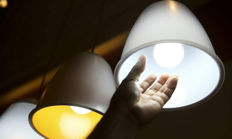 Homem confere lâmpada. Custo extra da energia se manterá em patamar alto (Foto: Agência Brasil)