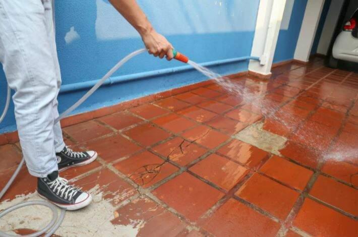 Rapaz usa água e mangueira para limpar quintal. (Foto: Arquivo)