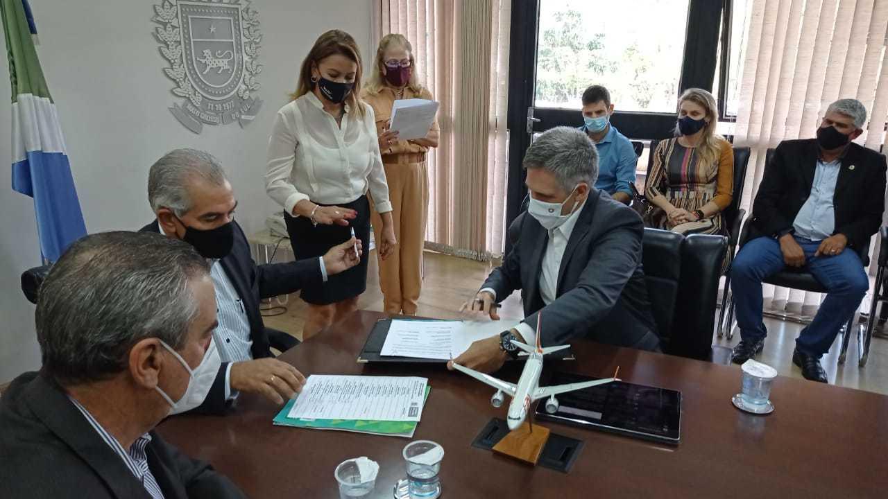 Momento em que o governador Reinaldo e o presidente da Gol, Paulo Kokinoff, assinam o acordo de operação da empresa em Bonito (Foto: Gabriela Couto)