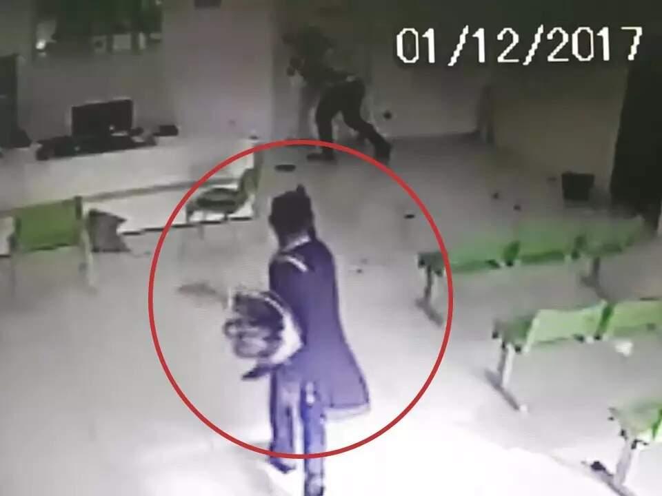 Wellington de Almeida com capacete no braço, enquanto atira nas pessoas. (Foto: Reprodução do vídeo de câmera de segurança)