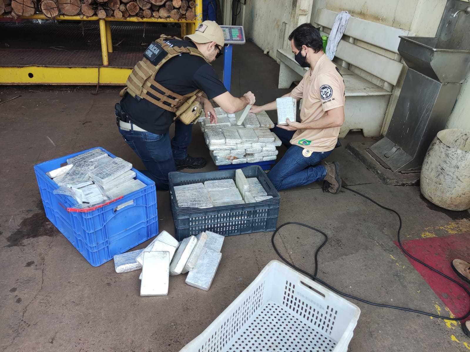 Policiais com os tabletes de cocaína, que foram incinerados durante a operação desta terça-feira (14). (Foto: Polícia Civil)