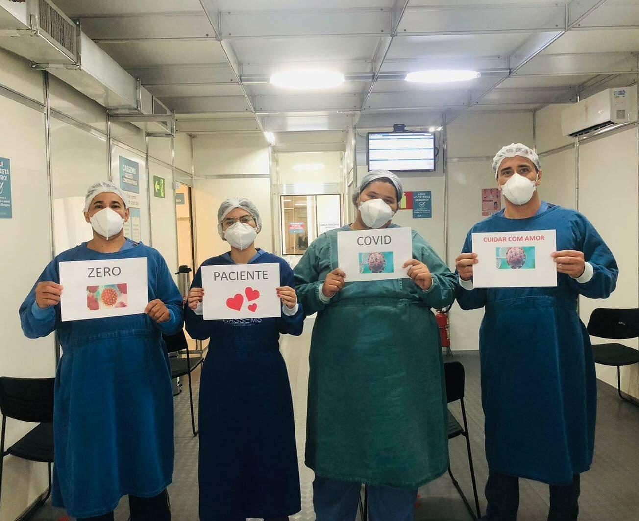 Profissionais da saúde seguram cartazes com os dizeres sobre a falta de pacientes com covid no hospital. (Foto: Cassems/Reprodução)