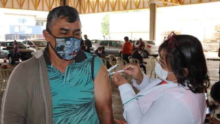 Homem recebe dose de vacina contra covid em ação itinerante. (Foto: PMCG/Divulgação)