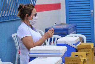 Profissional da saúde manuseando vacina em ponto de imunização, em Campo Grande. (Foto: Paulo Francis)