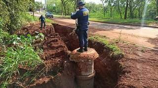 Guarda faz foto em local onde buraco começa a invadir asfalto. (Foto: Sidnei Bronka/Ligado na Notícia)