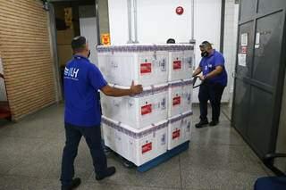 Funcionários manuseiam lote com vacinas da Coronavac. (Foto: Paulo Francis/Arquivo)