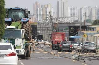 Caminhão carregando trator e carro de idosa ficaram enroscados em fios elétricos (Foto: Marcos Maluf)