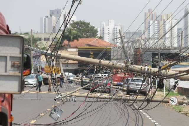 Caminhão derruba fileira de postes e idosa é resgatada de carro coberto de fios