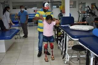 Pai ajudando filha a caminhar com a nova prótese. (Foto: Assessoria Apae)