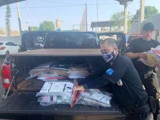 Policiais recolhem documentos apreendidos durante Operação Dark Money (Foto: Divulgação)