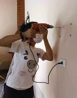 """Michelly furando a parede em um dos seus serviços de """"Marida de Aluguel"""". (Foto: Arquivo Pessoal)"""