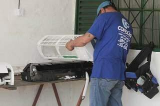 Funcionário realizando manutenção em aparelho em um loja. (Foto: Marcos Maluf)