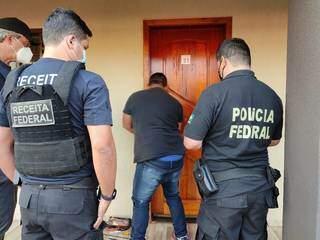 Agentes da Receita e da PF esperam abertura de quarto de hotel durante operação. (Foto: Divulgação)