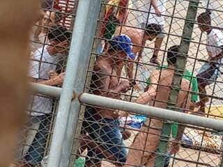 Encostado na parede, preso digita em celular tranquilamento durante banho de sol. (Foto: Direto das Ruas)