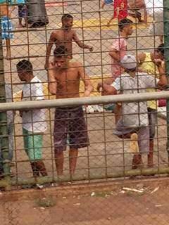 Na cerca, preso fala com alguém pelo celular. (Foto: Direto das Ruas)