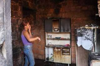 Ana Lúcia observa como a cozinha ficou após ser destruída pelas chamas (Foto: Henrique Kawaminami)