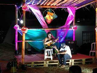 Bruna tocando ukulele com ajuda improvisada para que o som do instrumento ficasse mais alto. (Foto: Lidiane Antunes)