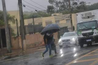 Pessoas caminham segurando guarda-chuvas. (Foto: Paulo Francis/Arquivo)