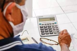 Homem faz cálculos para organizar o planejamento financeiro do mês. (Foto: Henrique Kawaminami/Arquivo)