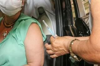 Mulher se prepara para receber dose da vacina contra covid-19. (Foto: Henrique Kawaminami)