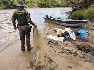 Policial Militar Ambiental recolhendo petrechos de pesca ilegal durante operação. (Foto: Divulgação)