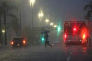 Mulher atravessa Afonso Pena tentando se proteger da chuva. (Foto: Henrique Kawaminami)
