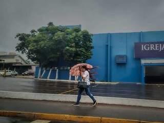 Mulher se protege da chuva com guarda-chuva na Avenida Eduardo Elias Zahran. (Foto: Marcos Maluf)