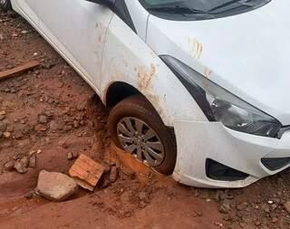 Carro ficou com para-choque danificado após queda no buraco. (Foto: Direto das Ruas)