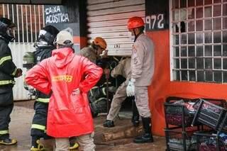 Bombeiros tiveram que arrombar loja ao lado. (Foto: Henrique Kawaminami)