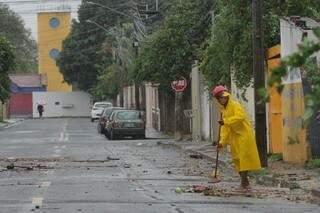 Homem aproveitando momento de trégua da forte chuva para limpar sujeira que ficou para trás. (Foto: Marcos Maluf)