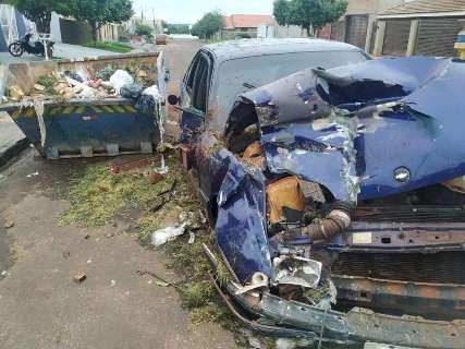 Motorista perde controle da direção e carro fica destruído após bater em caçamba