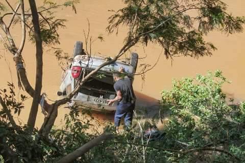 Condutor bate carro em poste, atinge árvore e vai parar dentro de córrego