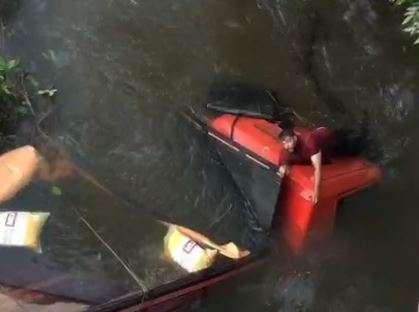 Vídeo mostra motorista saindo de cabine após cair com caminhão em córrego